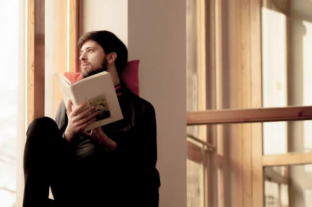 梅雨空を見ながら本を読む男性